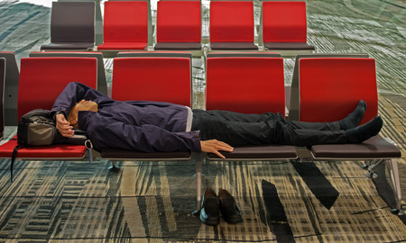 induced: Changi Airport Singapore - November 7 2014 - Weary traveler taking a nap due to jet lag. Jet lag is a chronobiological problem, similar to issues often induced by shift work.