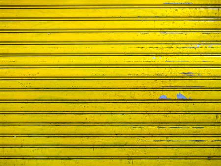 close up of grunge bright yellow roller shutter door texture background photo