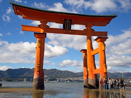 shinto: MIYAJIMA HIROSHIMA, JAPAN NOVEMBER 10, 2015: The famous orange floating shinto gate (Torii) of Itsukushima shrine panorama, Miyajima island of Hiroshima prefecture, Japan during low tide.