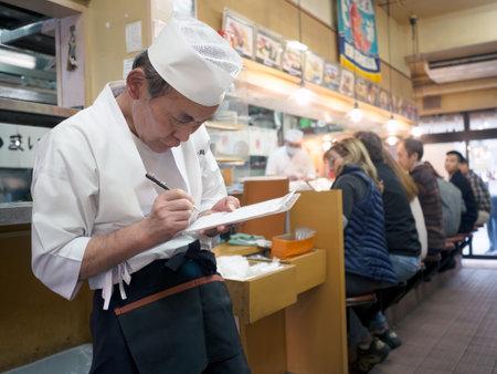 freshest: Tokyo, Japan - November 12, 2015: Waiter at sushi restaurant around Tsukiji fish market. Tsukiji is the biggest fish market in the world. The restaurants serve the worlds freshest sushi.
