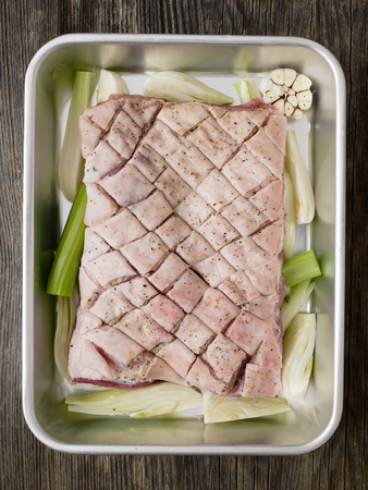 scored: close up of rustic raw uncooked seasoned pork belly