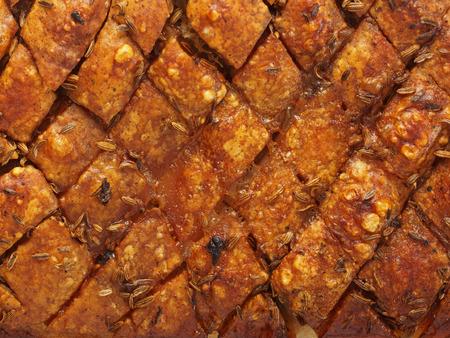 scored: close up of rustic scored golden roasted pork belly skin background