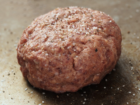 seasoned: close up of rustic uncooked seasoned hamburger patty