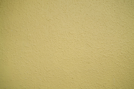 close up of pastel yellow plastered wall texture background