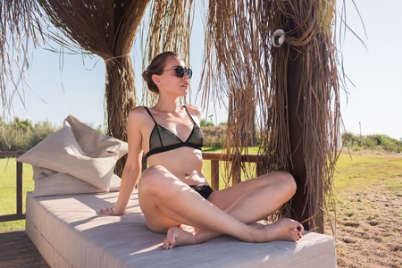 sunbath: Beautiful young girl in bungalow with sunglasses and black swimsuit having sunbath Stock Photo