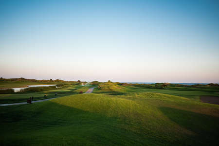 Loopbrug in de buurt van golfbaan met meergevaar en zee op de achtergrond bij zonsondergang