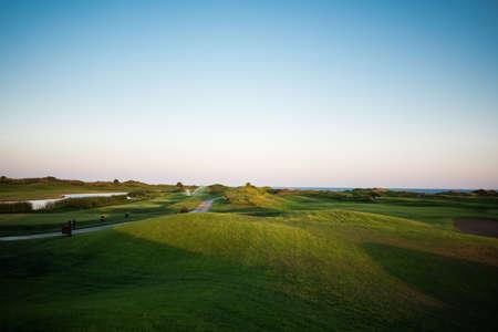 Pasarela cerca del campo de golf con peligro de lago y mar de fondo al atardecer