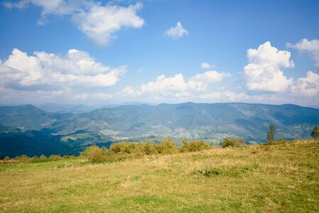 Top of the hill in Carpathian mountains. Beautiful blue sky with clouds in the background. Summer time.