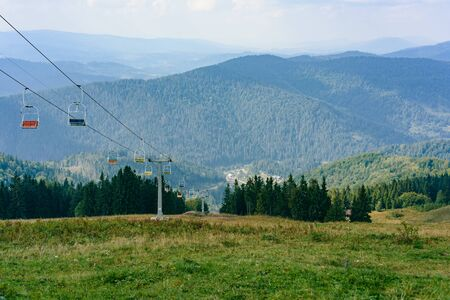 Lift in the Carpathians with mountains and fir-trees in the background. Summer time