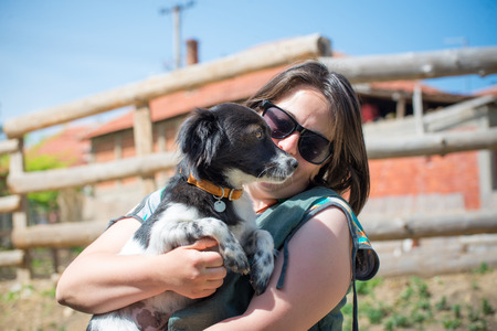Young  woman with sun glasses hug her small mixed-breed dog