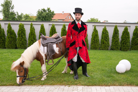 Young gentleman with top hat and his pony posing for a photo