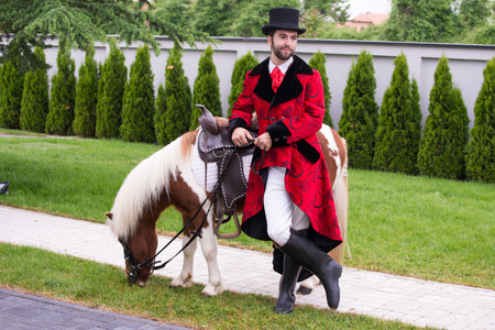 Gentleman with beard and top hat with his pony posing for a photo