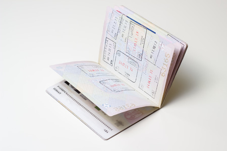 Isolated open foreign passport with visa stamps. photo