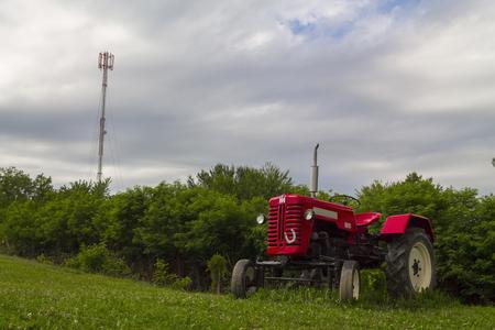 arando: Tractor rojo en el campo en un día nublado Foto de archivo