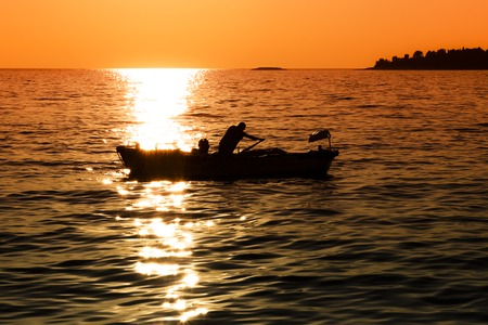Small boat and a man at sunset in Croatia Stock Photo