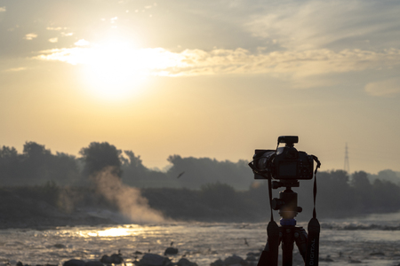 Camera on a tripod shooting at sunrise