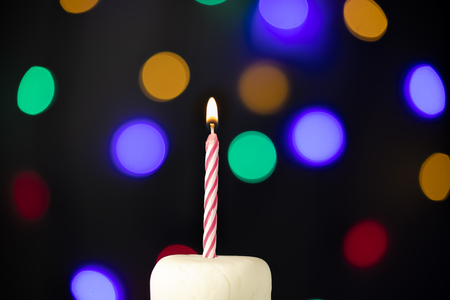 Birthday candle on a white cake with colorful lights in the background Stock Photo