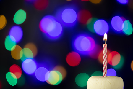 Birthday candle on a white cake with colorful lights in the background Stock Photo - 114657857