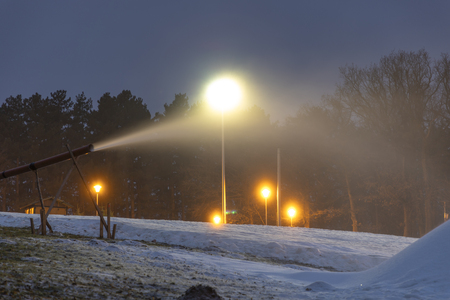 Snow canon makes snow at night Stock Photo