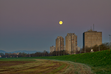 Moon setting down in the morning behind buildings in Zagreb