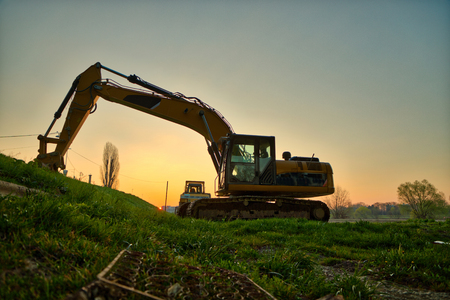 Yellow excavator at sunrise by the river bank Stock Photo