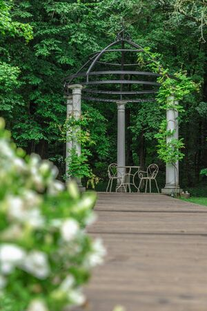White gazebo for weddings in the woods on a cloudy day