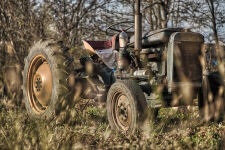 Old vintage rusty broken tractor in a field on a sunny day Stock Photo
