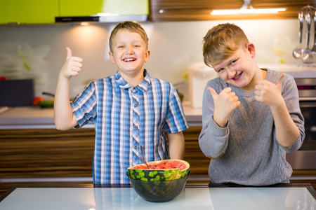 Happy little kids eating watermelon in the house and putting likes 写真素材