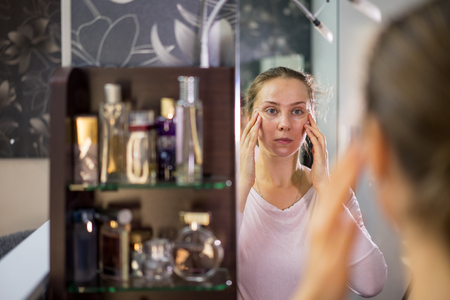 Woman of middle age in the bathroom mirror at the make-up 写真素材 - 113672573