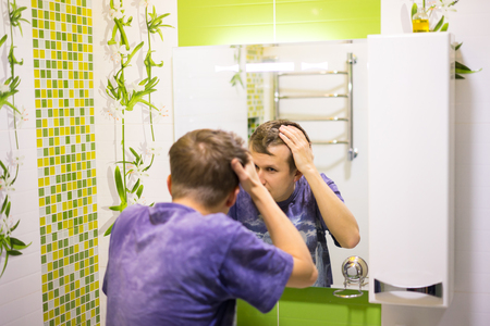 Dandruff on the head. Young man in the restroom room