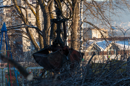 In the city, trees fell. Crane manipulator collects pieces of wood from the road. CMU bucket manipulator. Hydraulic instrument. Machine industry. Standard-Bild