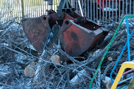 Cleaning felled trees from city streets in winter. CMU bucket manipulator. Hydraulic instrument. Machine industry. Standard-Bild