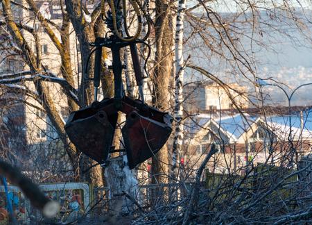 Excavator cleans sawed trees in the city in winter. Standard-Bild