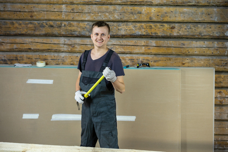 A construction worker is smiling cheerfully at the camera. In his hands he holds a tape measure, what size is needed?