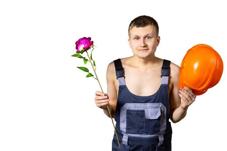 A nice professional builder congratulates all women on March 8, International Women's Day. Macho with a rose and a helmet in his hands on an isolated background.
