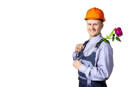 A cheerful smiling man builder on a white background with a rose in his hands congratulates everyone on the holiday. World Women's Day, March 8, the day of celebration, anniversary, holiday. Isolated