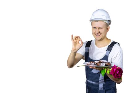 A male builder shows with a hand gesture that everything will be fine. He treats everyone with cookies and gives a rose. Congratulations to women or men for any occasion. Isolated Reklamní fotografie