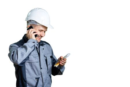 A builder in a white helmet on a white background talking on the phone and looks at the money in his hands. Great day for salary. Isolated