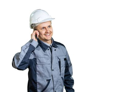 The builder is talking to someone on the phone. The working man pondered something good. The future is in our hands. Isolated