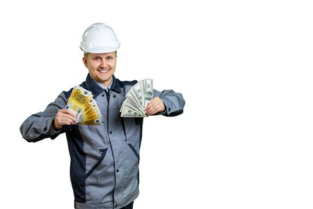Builder engineer holds money in both hands. Dollars and euros. Today he made a fortune by repairing or building a building. Isolated