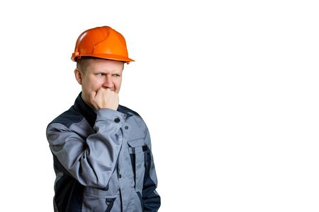 A construction engineer in an orange helmet did something wrong with a construction site. He is afraid that he will get from the boss