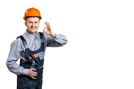 Builder in an orange helmet with a gesture, everything is fine. Workers at a construction site are ready to repair. All construction will be done in a better way. isolated Reklamní fotografie
