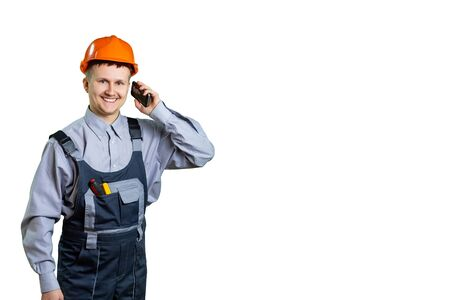 Architect or builder engineer smiling at you, construction worker in orange helmet talking on a mobile phone. Isolated. Banco de Imagens