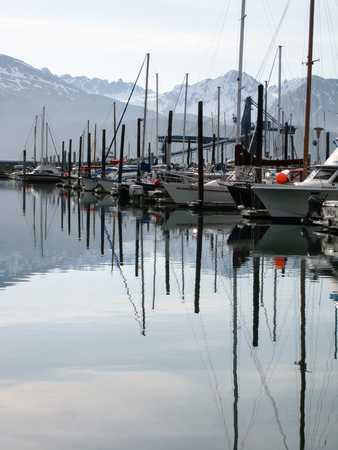 Boats anchor in still water with snowcapped mountain on background of Seward harbor in Alaska in the early morning.