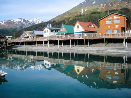 Many shops located at the waterfront of the Seward boat harbor reflect in the still water .