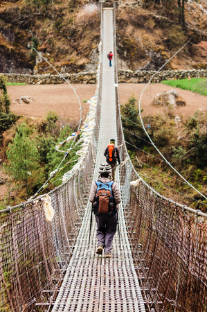 swaying: Every trekker is crossing a canyon by a long rope bridge with prayer flags on the everest base camp trekking route. Stock Photo
