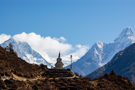 View of a Buddhist stupa with mountain Ama Dablam behind on the way from Namche Bazaar to Tengboche of the everest base camp trekking route.