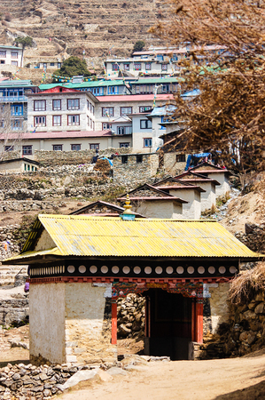 terracing: The gateway with yellow roof in front of the entrance of Namche Bazaar with housing on hillside terracing on background. Stock Photo