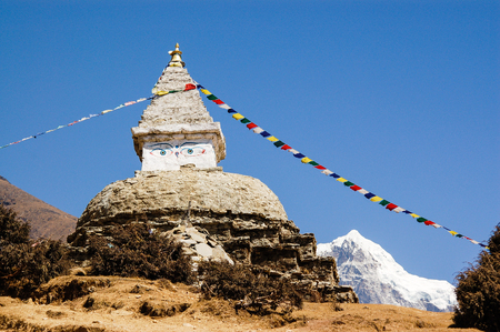 Buddhist stupa and colorful prayer flags with blue sky on the acclimatization route at Namche Bazaar in everest region of Nepal.