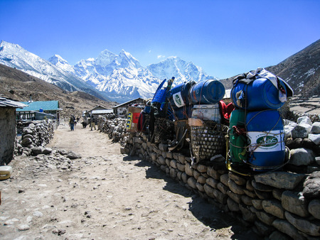 belongings: Belongings was placed on a stone wall in a village of himalayas with high snow mountains on background, waiting for transport to their destinations in a blue sky day. Editorial